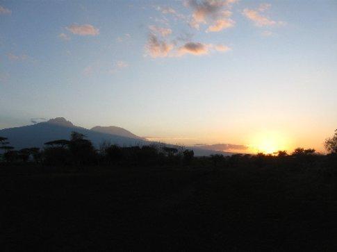 The sun sets over the Kenyan bush, leaving a sillhouette of majestic Mount Kilimanjaro.