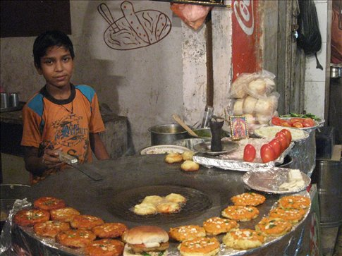 A new friend fries up veggie burgers for us on the streets of Amritsar