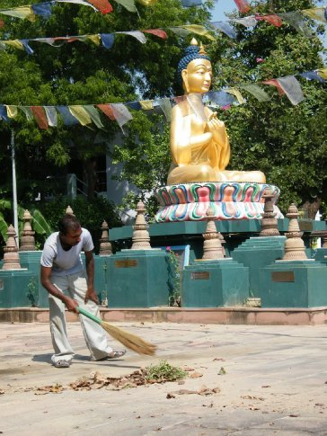 Indian man sweeping in front of a statue of Maitreya, an enlightened man (Buddha) expected to come in the future. The statue is at the Root Wisdom Institute -- a beautiful retreat center built by Gelukpas (a lineage of Tibetan Buddhism) in Bodhgaya.