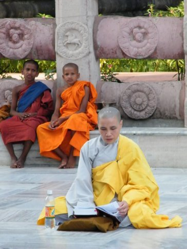 In addition to many lay pilgrims, the Bodhi Temple at Bodhgaya attracts Buddhist monastics from every nation and every tradition. Here, a Japanese Zen nun prays while Southeast Asian Therevadan monks look on.