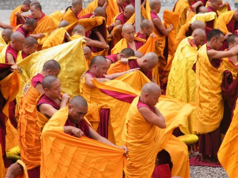 Monks at Gyutoe Monastery wrap in a final layer before entering the daily puja (offering) ceremony.