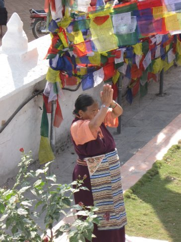 A Tibetan woman, in a beautiful traditional apron, expressing her devotion to the Buddha at Bodhnath stupa.