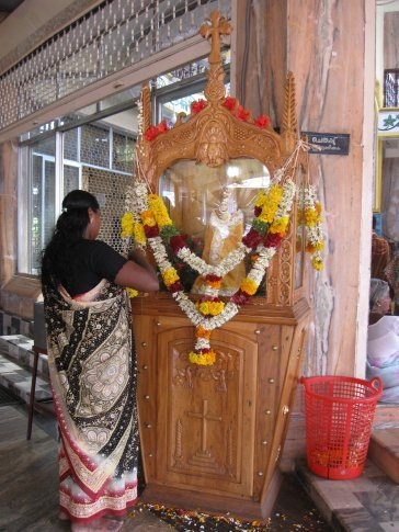 All over South India there are shrines from all faith traditions where people stop throughout the day to offer sacrifice and prayer.  Here, a Christian woman at a shrine to Our Lady of Health of Vailankanni.