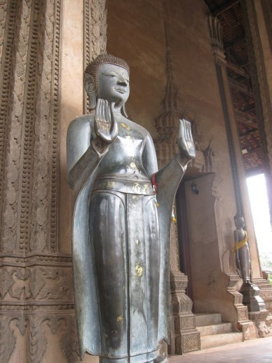 In a pose commonly seen in Southeast Asia, the Buddha stands in front of Haw Pha Kaeo.