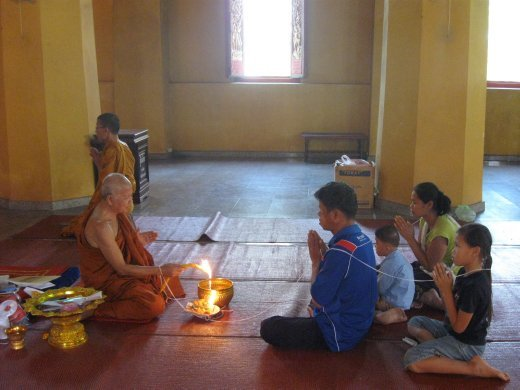 A family receives a blessing from a monk at Wat Ong Teu Mahawihan in Vientiane.