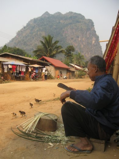 A man in Nong Khiaw cuts bamboo slats to weave sticky rice containers and other bamboo items.