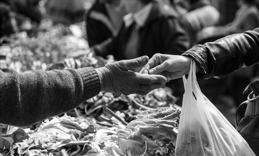 The old lady is returning change to a woman after buying vegetables