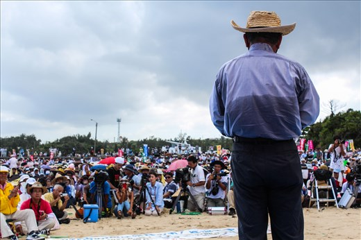 An activist outside the construction site of a new U.S. military base addresses a crowd of over 5,000 protesters. Okinawa is Japan's southernmost prefecture and although it only makes up 0.6% of Japan`s total land mass it houses 75% of the country's U.S. military base presence. The newest base is currently under construction in Henoko, Northern Okinawa, as part of a relocation deal to close down the controversial Futenma Air Station in the densely populated Ginowan City. However, many Okinawans are opposed to the plan and want the base moved out of the prefecture altogether. Mr. Onaga, a strong opponent of the relocation plan won the recent prefectural elections by a significant margin campaigning on an anti-base platform.