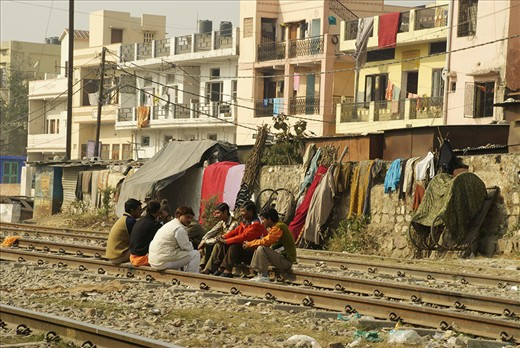 The tracks make perfect benches when it's break time for the men who live in and near the slums of Haridwar, India.