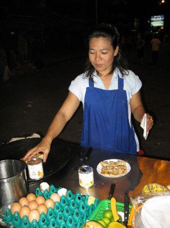 Street vendor on Khao San Road making delicious pancakes with egg, banana & chocolate