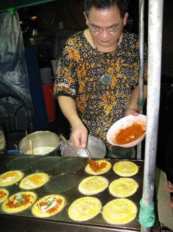 A popular chinese street vendor making me sweet and savoury pancake-like snacks