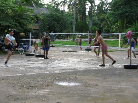 A group of police officers playing a variation of volleyball, using anything except hands. Thai people are supposedly very good at this game.