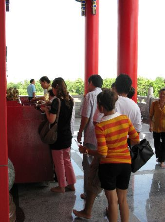 People queuing eager to make donations at the chinese Temple opposite the Nonthaburi market.