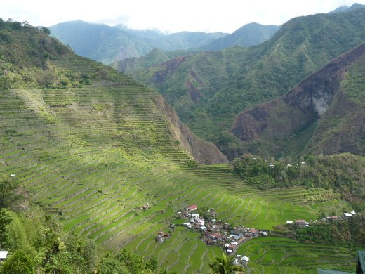 the tiny village of batad nestled beneath the enormous misty mountains and incredibly carved 2000 year old rice terraces...