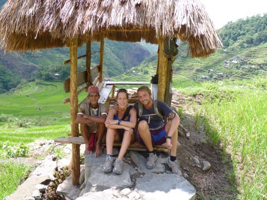 us and a local minority rice farmer in a traditional shelter