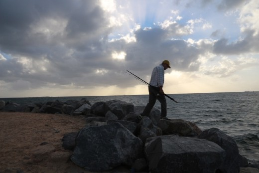 A causal fisherman at work. After the day job, a man is seeing carrying a fishing rod, still lingering on his hobbies with sunset at the background.