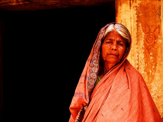 The weathered face of the old woman with its wrinkles and fine lines reiterate t