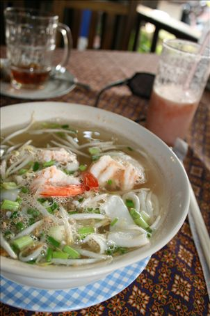 Watermelon shake in background and Prada sunglasses, foreground, typically spicy clear soup containing shrimp and pork, crunchy beansprouts and flat noodles
