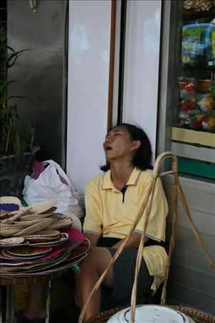 Bankok street vendor sleeping - either that or she's passed away from the sewage stench.
