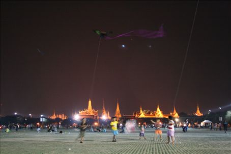children fight for air supremacy during the windy month of March.  The spectacularly lit Grand Palace lies behind the Park.