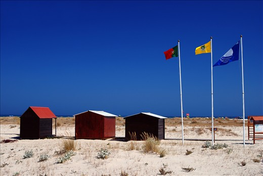 Isle of Tavira is one of the most popular tourism destinies for Camping lovers in Portugal. Three Flags represent Portugal, Algarve region and the town of Tavira, as well as openness to naturism and Camping.