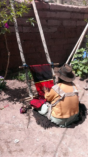 Sucre - local woman weaving in her yard in town in crater