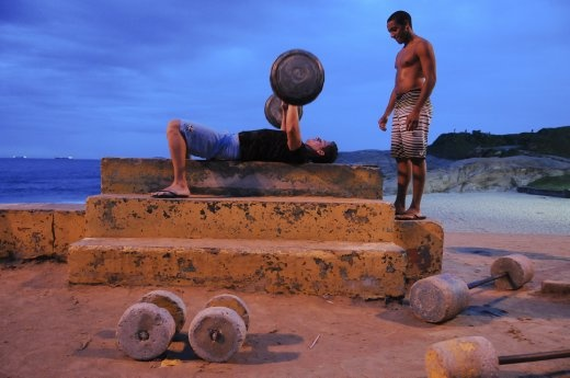 Black and white friends train together at a makeshift gym near Copacabana beach in Rio de Janeiro.