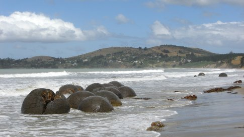 Moeraki Boulders, West Coast.  According to Maori legend, the boulders are gourds washed from the great voyaging canoe Araiteuru when it was wrecked upon landfall in New Zealand some 1000 years ago.   How wrong there were!  They're actually made from the Crystallisation of calcium and carbonates around charged particles in muddy undersea sediments gradually formed the boulders in a process taking as long as four million years!!! So there!!