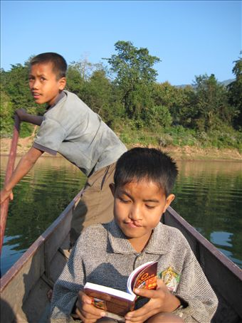 A young reader on the Nam Ou river