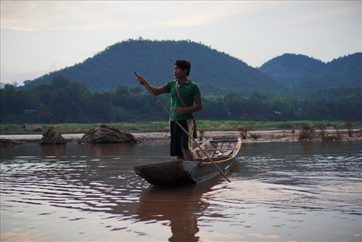 A young man heads home after a day's work in Luang Prabang. The Mekong is the highway, breadbasket and playground of the people who live in settlements along its banks. From childhood, they are taught to work with the natural rhythms of the river, learning to maneuver their long, low boats through the river's flow with confidence and ease.