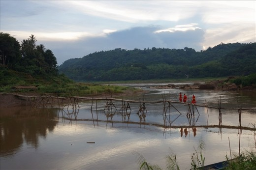 Monks walk across a bamboo bridge over a tributary to the Mekong.
