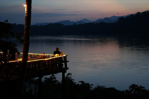 A man winds down in a restaurant overlooking the Mekong. Strict development regulations a midnight curfew maintain the relaxed character of Luang Prabang, which gained UNESCO World Heritage Site status in 1995.