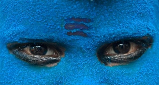 Artistic eyes of a Devotee sadhu of Lord Shiva at Maha Kumbh Mela at Haridwar.  The city of haridwar is flooded with thousands of saints all over the world and the atmosphere near the ganges river is filled with their hymes and prayers to please the God. It is among this we found such priest which had colored his face blue with three lines on his fore head  disguising himself into one of the devotees of Lord Shiva. His face gives a sense of cold glaciers and also like poison effect on his face and eyes.Just as lord Shiva turned blue after drinking the poison out of the whole world. This picture shows a sense of religious faith in god and its divine power