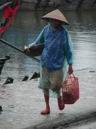 Old Lady walking down the street. A light rain.