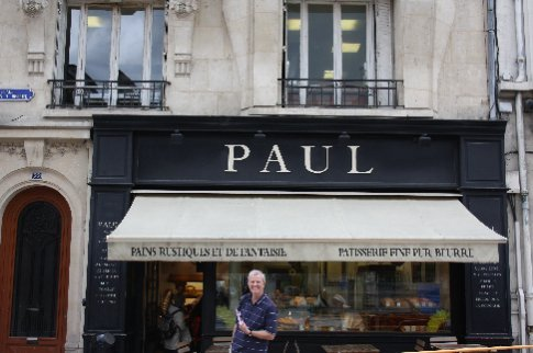 Paul outside one of the many stores in his French boulangerie chain.