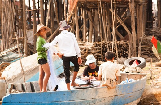 Everyone has their own role to play in the fishing 'production line' in the village and here the boys are busy untangling and mending the fishing nets.  In the background the stilt legs of the houses tower above the boat.