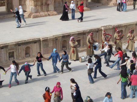 Jordanian schoolgirls dancing to scottish bagpipes in the roman ruins of Jerash