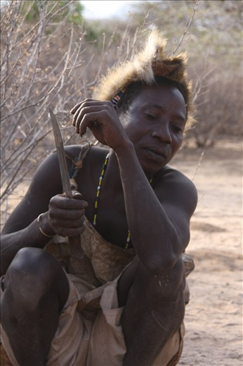 The tribesmen wait patiently to carve the Dik Dik on the fire.