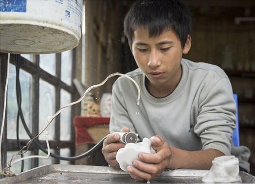 A teenage boy focuses on polishing up his