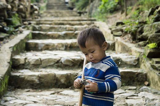 A local Hmong boy ponders at a granola bar that was given to him by a friendly visiting tourist.