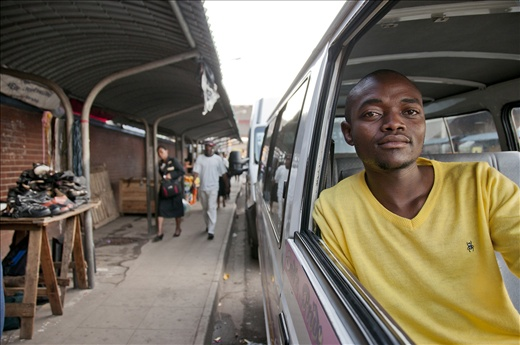 Taxi driver awaits passengers to be transported from the market.