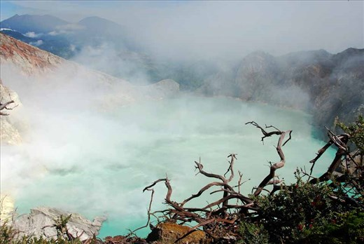 Stunted trees line the rim of the Mt Ijen crater in East Java, while sulphur-drenched volcanic fumes drift over the azure lake.