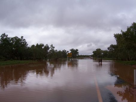 Flooded road with Aboriginal children swimming in it