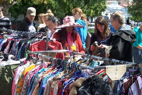 Kate (in hat) talking to customers at her sunday market clothes stall