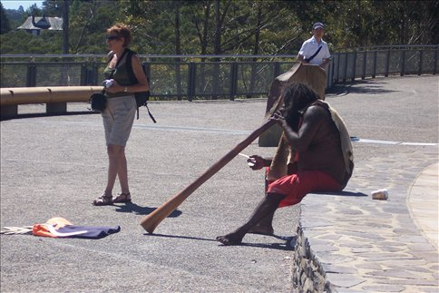 Aboriginal man playing digeridoo at a Blue Mountains viewpoint