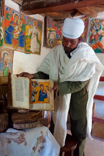 priest displaying 300 yr old Stories of Mary book