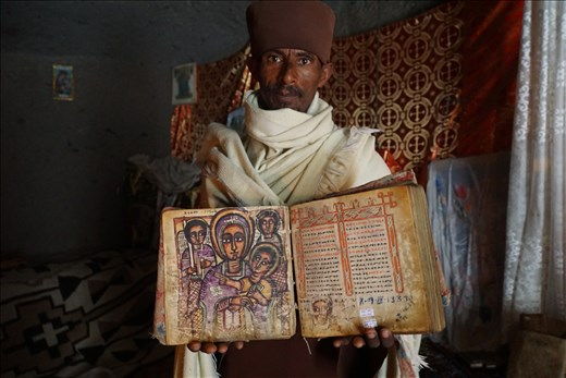 Priest holding 300 yr old Marian book