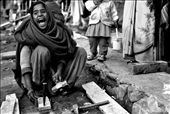 A young girl breaks firewood in a small slum in the Kathmandu Region, Nepal. Surprised to look up and notice me taking her picture she laughs in embarrassment and utters secrets to her girlfriends.: by lachlanmcgarvie, Views[614]