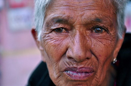 An elderly woman who has been financially supported by EPSA (Entire Power for Social Action) in Nepal poses for a photo in the streets of Kathmandu. This poor woman lives alone with no protection or security and continues to work and labour in order to survive.