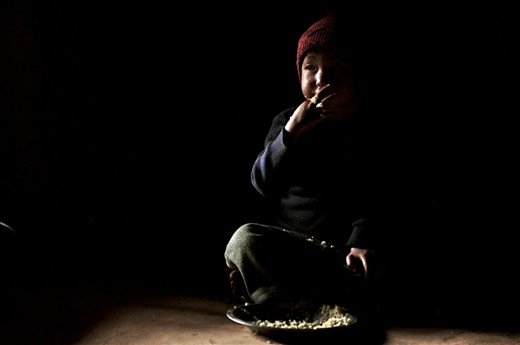 A young boy sits and eats his third meal of rice in his house in the mountain village of Dhading, central Nepal. The youngest boy of a family where the majority are disabled either physically of mentally from malnutrition and poverty.